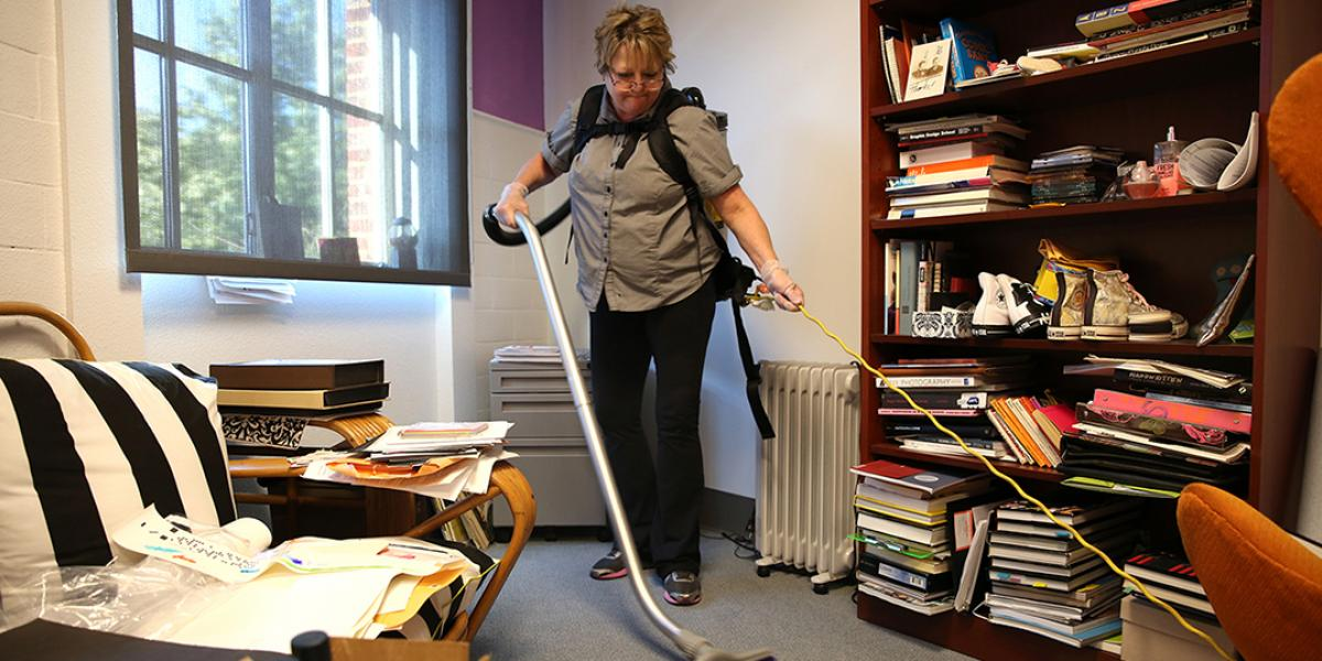 Custodial worker vacuums an office