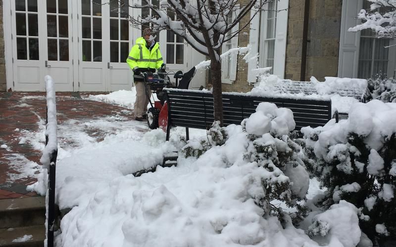 Crew member clears snow outside the Hintz Family Alumni Center.