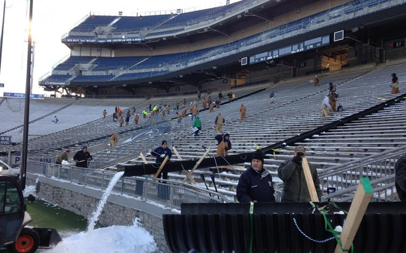 Crews work to clear Beaver Stadium of snow.