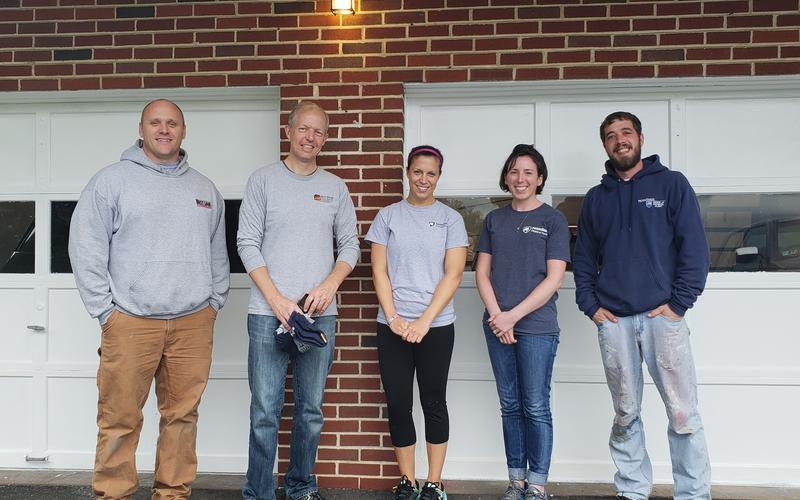 Volunteers in front of freshly painted garage