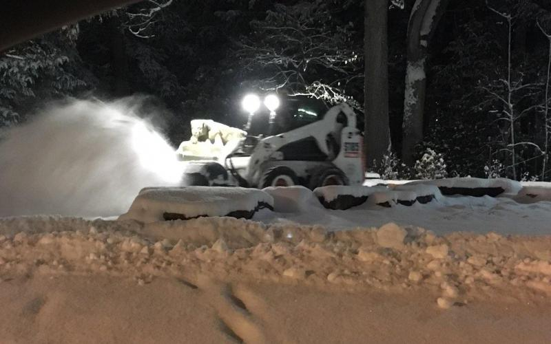 Snow brush cleans sidewalk