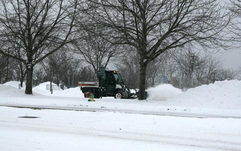 Snow brush cleans sidewalk near the BJC.