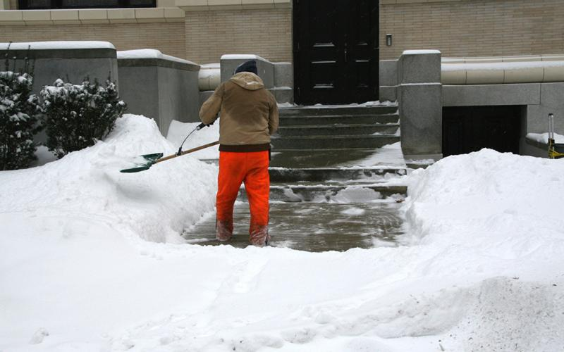 An OPP employee shovels snow