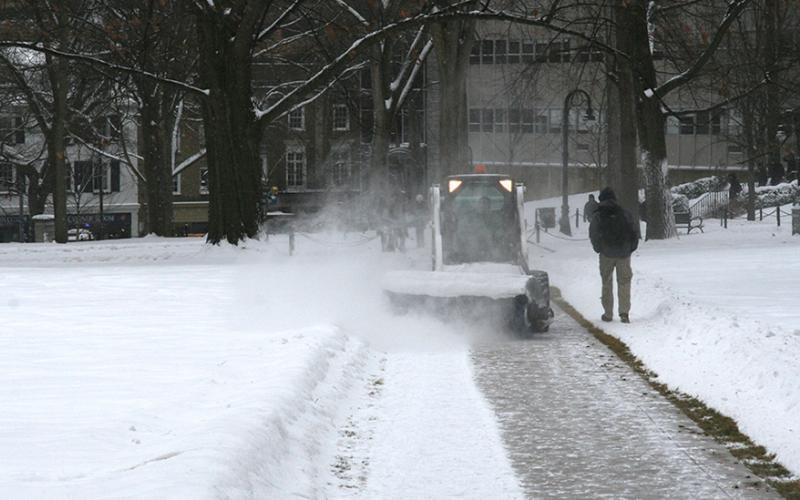 Snow brush cleans sidewalk near Old Main