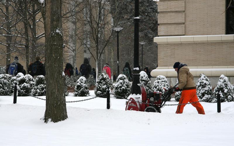 An OPP employee uses a snowblower
