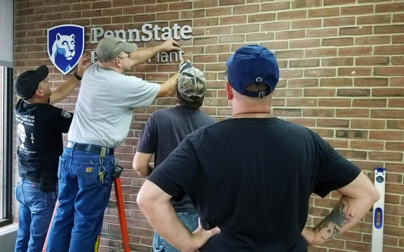 Photo of employees installing the new OPP sign.