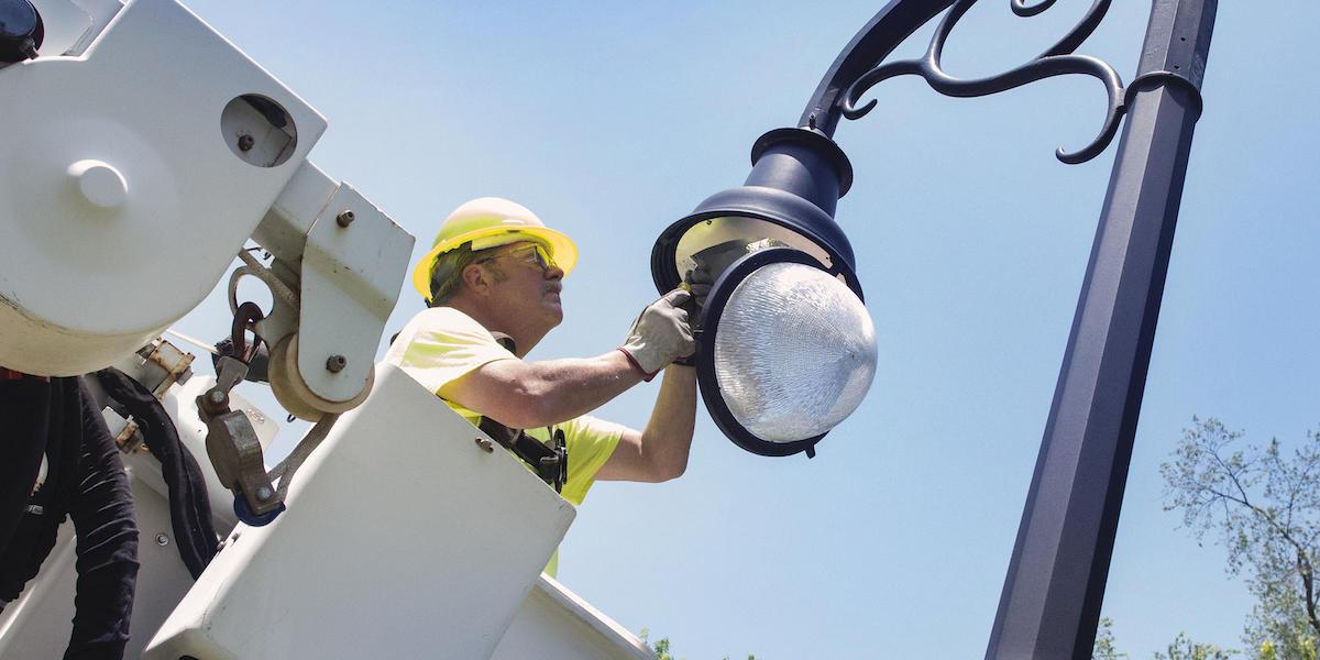 worker changes light fixture