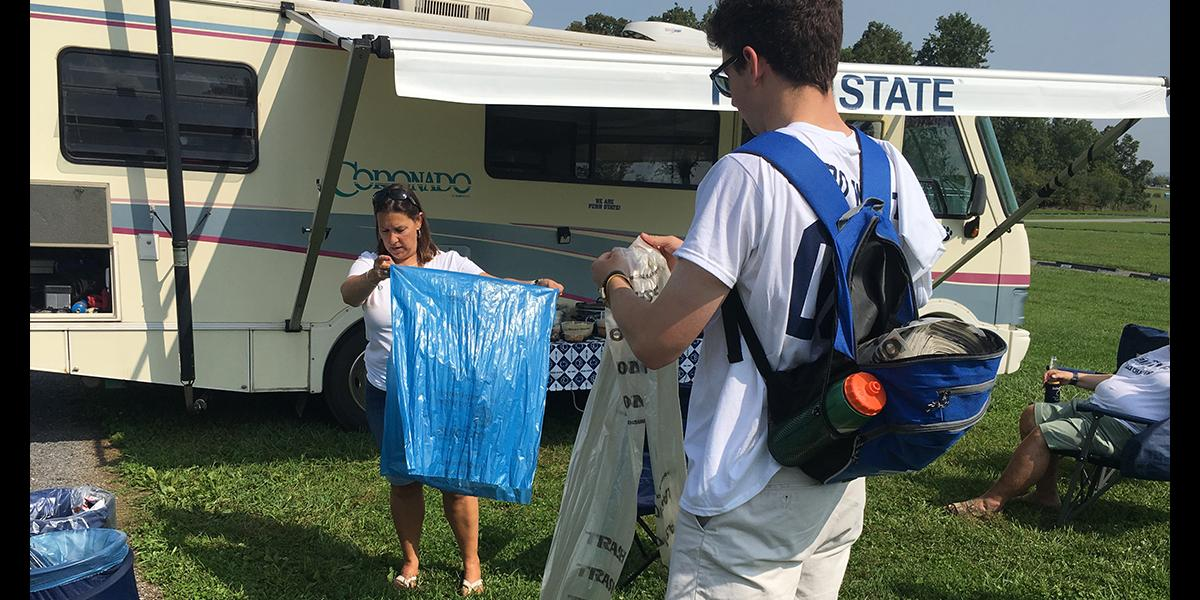 STudent offers recycling bag to tailgater